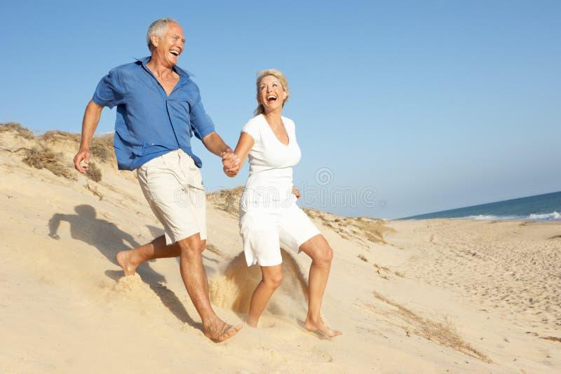 Pares mayores que disfrutan del funcionamiento del día de fiesta de la playa fotos de archivo