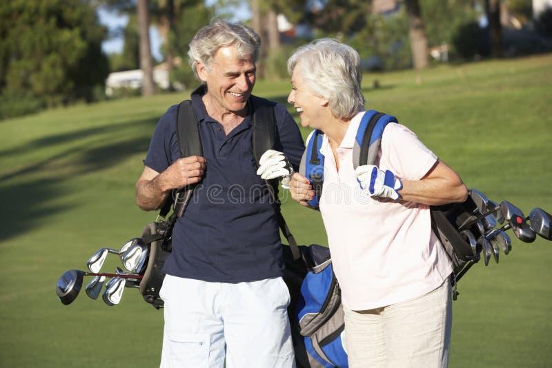 Pares mayores que disfrutan del juego del golf fotografía de archivo libre de regalías