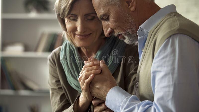 Pares mayores que disfrutan del momento feliz, llevando a cabo blando matrimonio acertado de las manos imagen de archivo libre de regalías