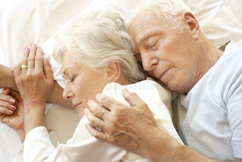 Pares mayores que duermen en cama fotografía de archivo libre de regalías