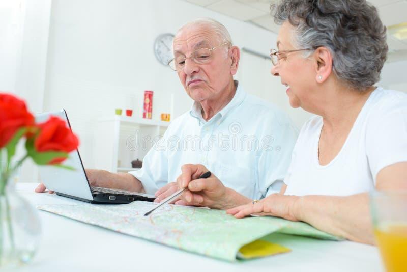 Pares mayores que estudian el mapa y que usan el cuaderno fotografía de archivo libre de regalías