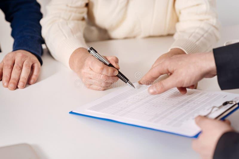 Pares mayores que firman el documento importante en casa imagen de archivo libre de regalías