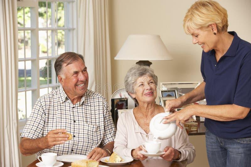 Pares mayores que gozan del té de tarde junto en casa con ayuda a domicilio fotos de archivo