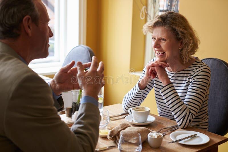 Pares mayores que hablan sobre el café y la comida en un restaurante imágenes de archivo libres de regalías