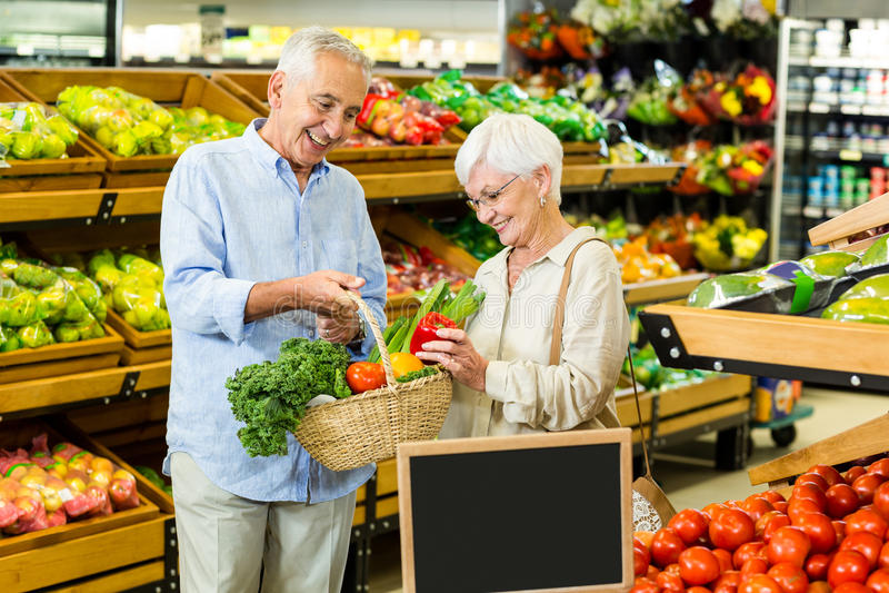 Pares mayores que hacen cierto hacer compras junto foto de archivo