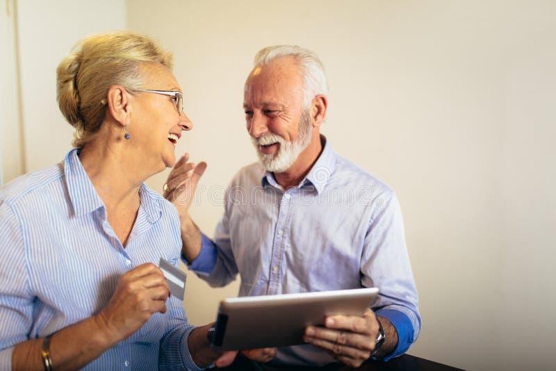 Pares mayores que hacen compras en línea con la tableta y la tarjeta de crédito foto de archivo