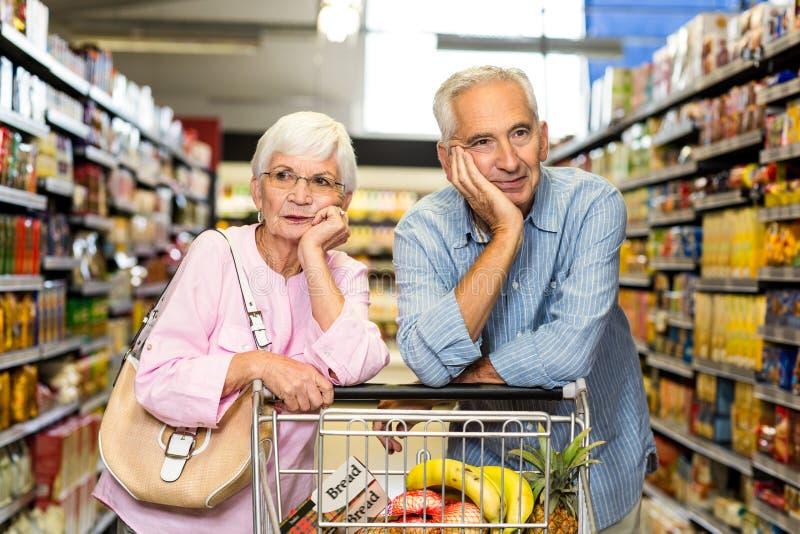 Pares mayores que hacen compras junto fotografía de archivo libre de regalías