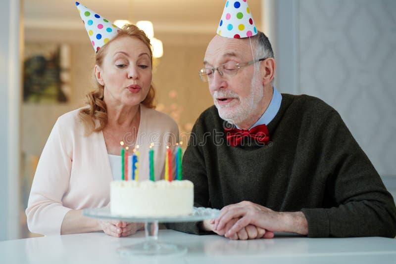 Pares mayores que hacen deseo del cumpleaños imágenes de archivo libres de regalías
