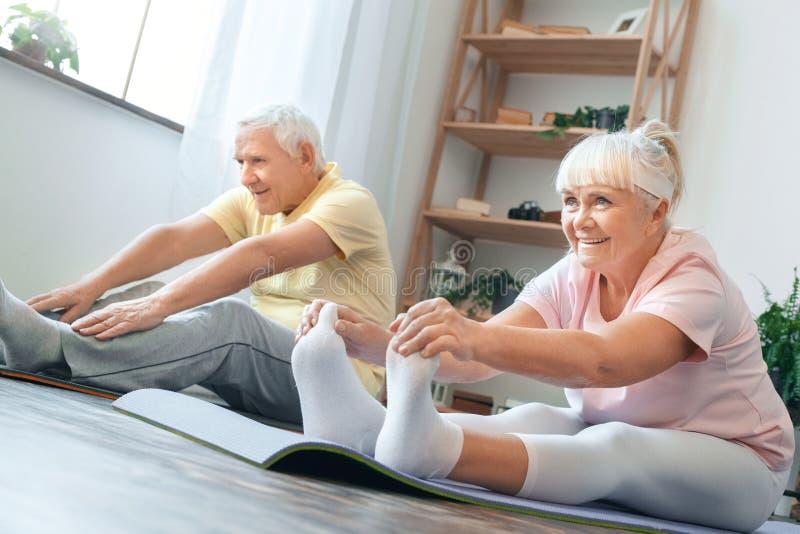 Pares mayores que hacen estirar de las piernas de la atención sanitaria de la yoga junto en casa imagenes de archivo