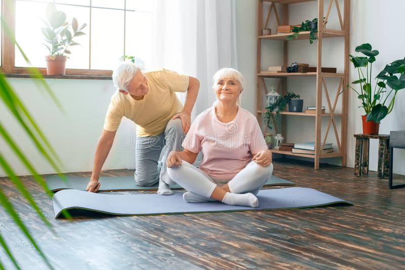Pares mayores que hacen la sonrisa de la actitud de la mariposa de la atención sanitaria de la yoga junta en casa fotografía de archivo libre de regalías