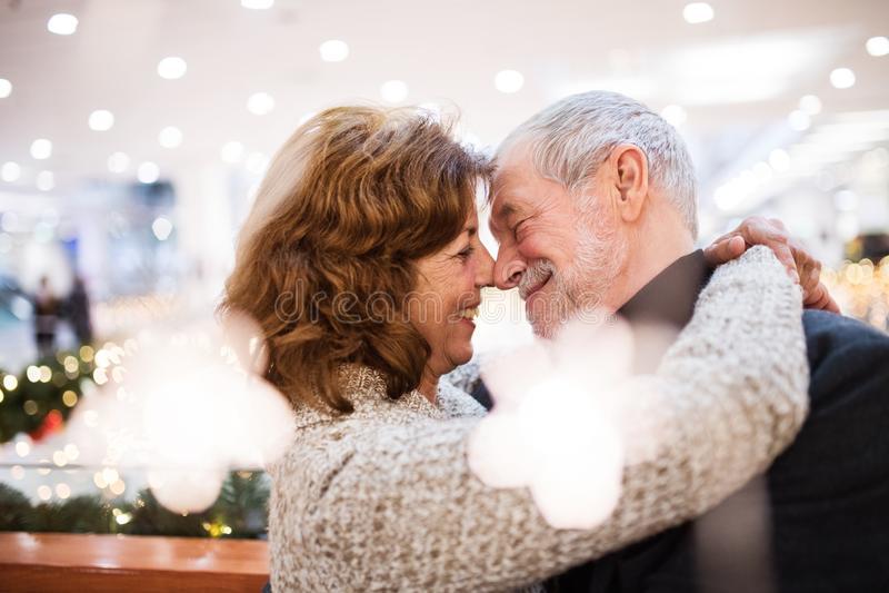 Pares mayores que hacen las compras de la Navidad, abrazando foto de archivo libre de regalías