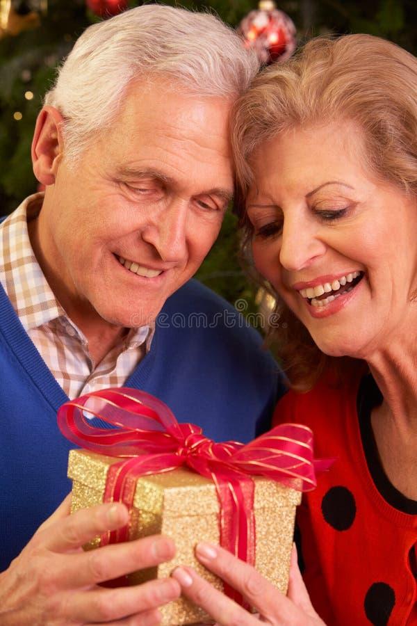 Pares mayores que intercambian los regalos de la Navidad imagenes de archivo