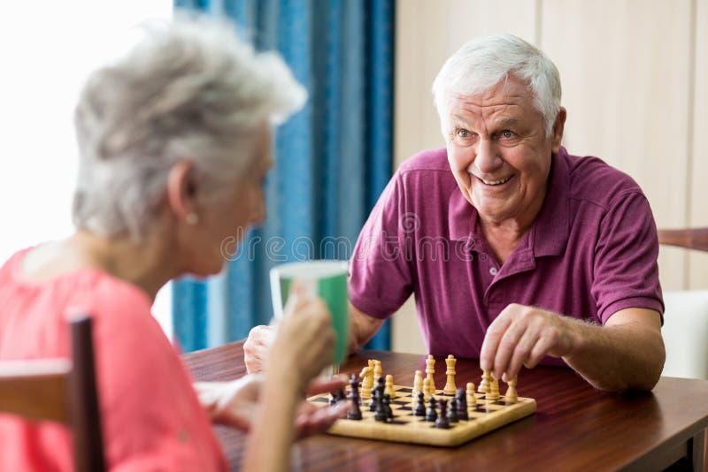 Pares mayores que juegan a ajedrez fotos de archivo
