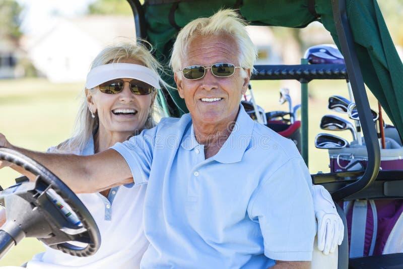 Pares mayores que juegan al golf que conduce el cochecillo del carro imagen de archivo