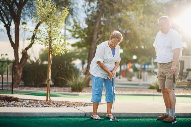 Pares mayores que juegan el mini tiro de golf con la llamarada de la lente fotografía de archivo libre de regalías
