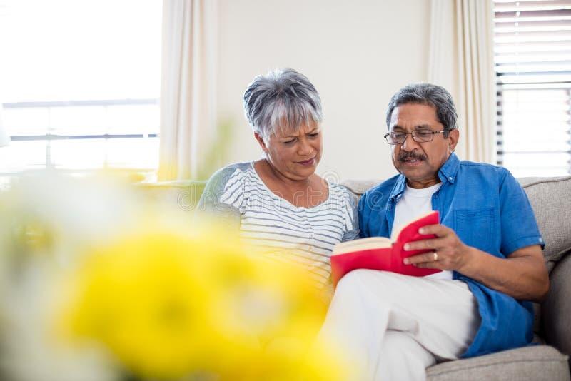 Pares mayores que leen una novela en sala de estar imagen de archivo libre de regalías