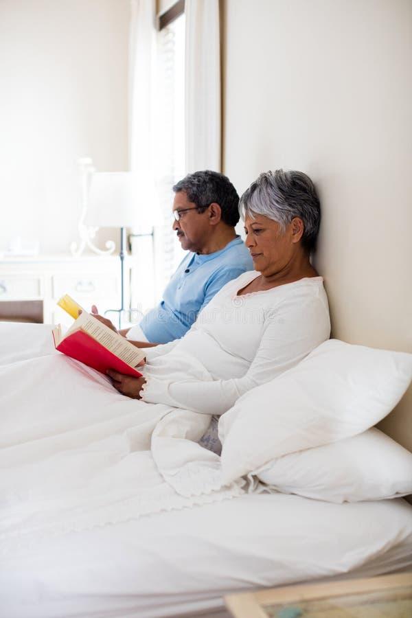 Pares mayores que leen una novela en sala de estar imagenes de archivo