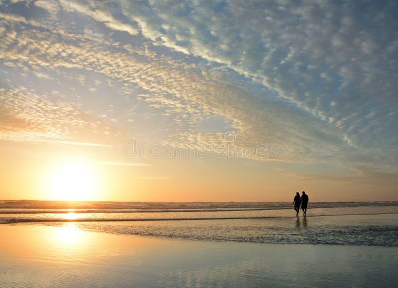 Pares mayores que llevan a cabo las manos que caminan en la playa que disfruta de salida del sol imagenes de archivo