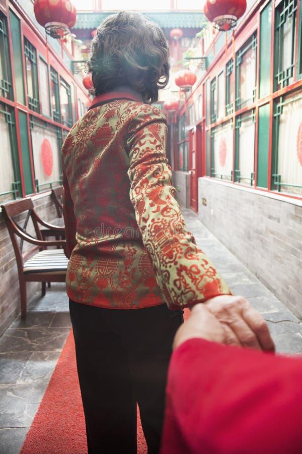 Pares mayores que llevan a cabo las manos, vista posterior foto de archivo