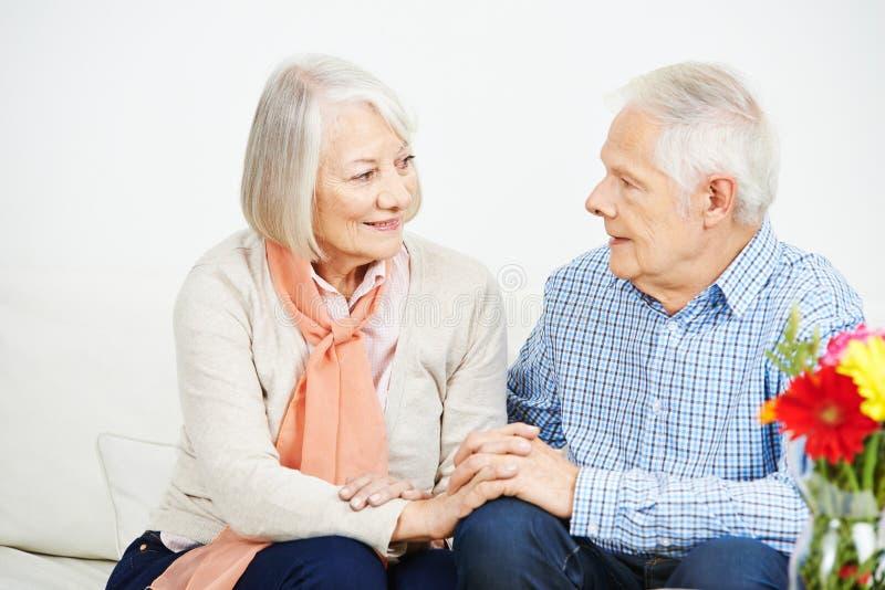 Pares mayores que llevan a cabo las manos y hablar foto de archivo libre de regalías