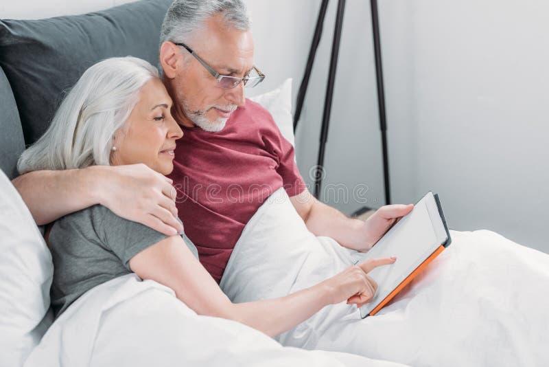 Pares mayores que mienten en cama y que usan la tableta junto fotos de archivo libres de regalías