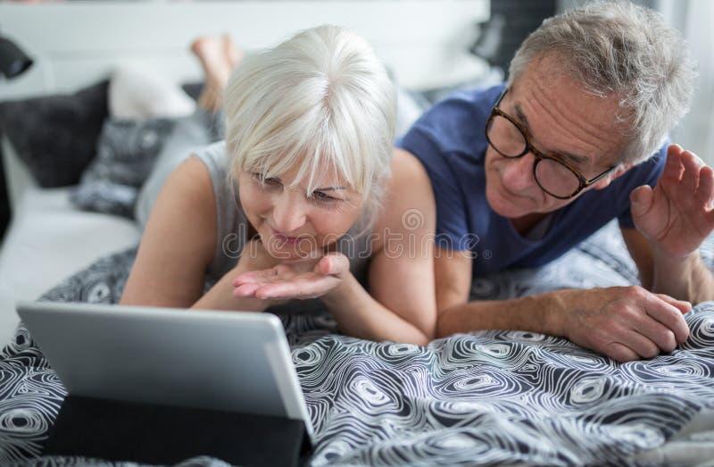 Pares mayores que mienten en la cama que tiene conversación video imágenes de archivo libres de regalías