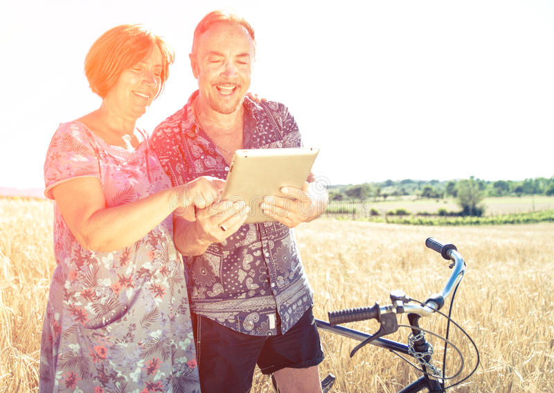 Pares mayores que miran algo en la tableta imágenes de archivo libres de regalías