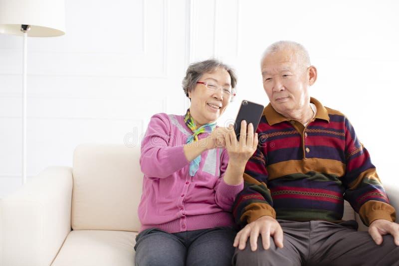 pares mayores que miran el teléfono móvil imagen de archivo