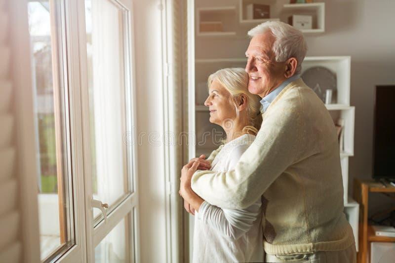 Pares mayores que miran hacia fuera la ventana de la sala de estar fotografía de archivo libre de regalías