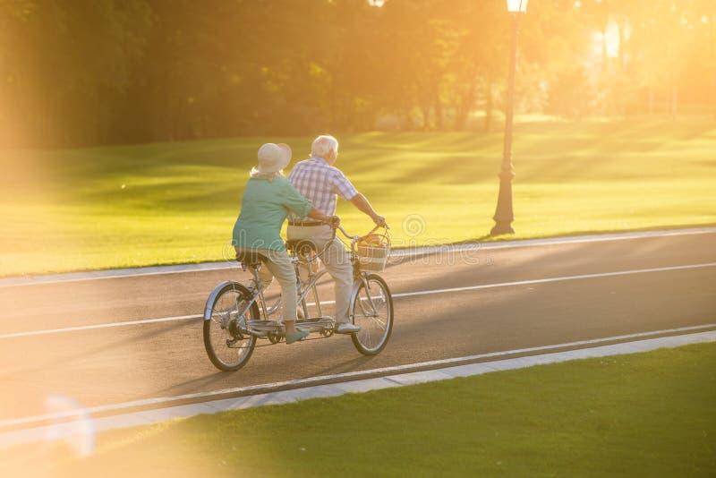 Pares mayores que montan la bicicleta en tándem foto de archivo