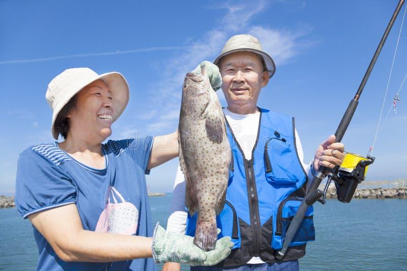 Pares mayores que pescan y que muestran el mero grande imagenes de archivo