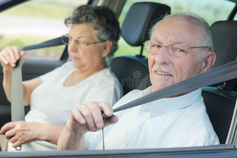 Pares mayores que ponen el cinturón de seguridad imagenes de archivo