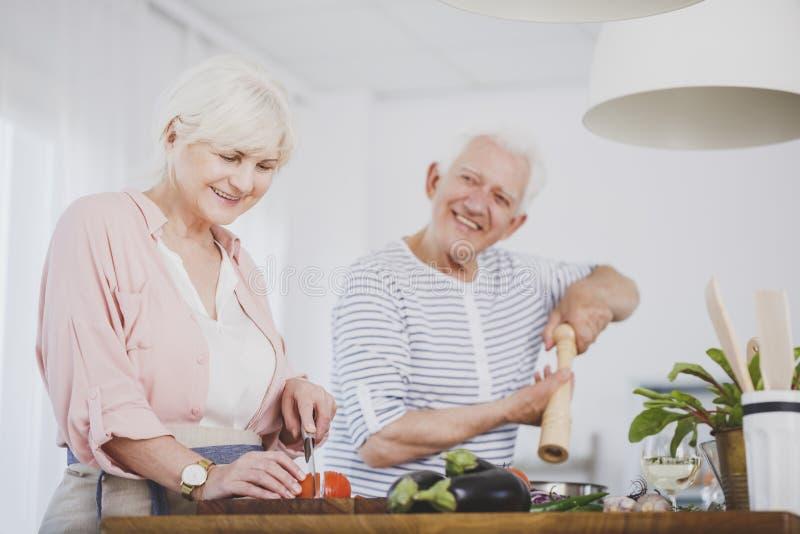 Pares mayores que preparan la comida sana imagenes de archivo