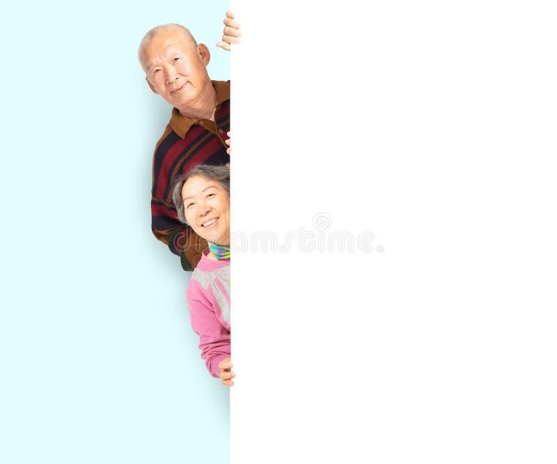 Pares mayores que presentan detrás del tablero blanco en blanco fotografía de archivo