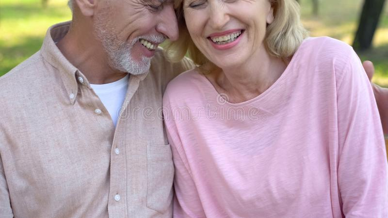 Pares mayores que ríen junto, disfrutando de la fecha romántica, entendimiento mutuo foto de archivo