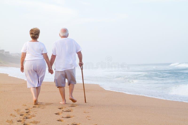 Pares mayores que recorren en la playa imagen de archivo libre de regalías