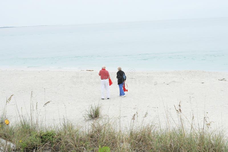 Pares mayores que recorren en la playa fotografía de archivo
