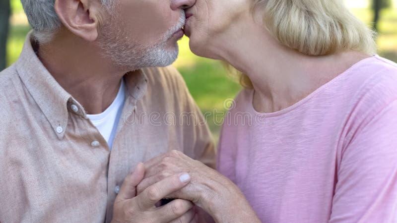 Pares mayores que se besan, matrimonio feliz, amor maduro, haciendo frente a edad avanzada junto fotos de archivo libres de regalías