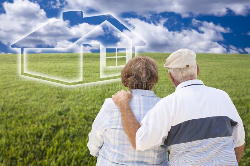 Pares mayores que se colocan en el campo de hierba que mira la casa de Ghosted imágenes de archivo libres de regalías