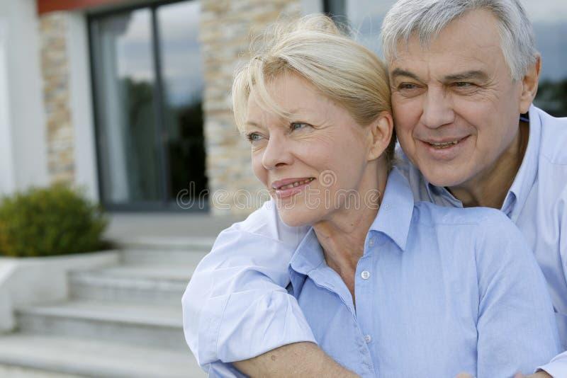 Pares mayores que se colocan en frente de su nuevo hogar foto de archivo libre de regalías