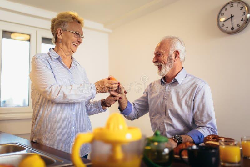 Pares mayores que se divierten que prepara la comida sana en el desayuno en la cocina fotografía de archivo