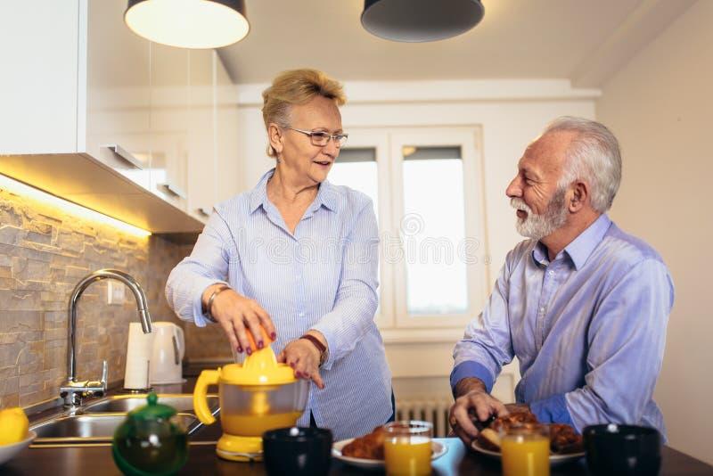 Pares mayores que se divierten que prepara la comida sana en el desayuno en la cocina fotos de archivo libres de regalías