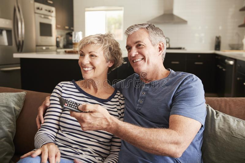 Pares mayores que se incorporan en la televisión de observación del sofá, cierre imágenes de archivo libres de regalías