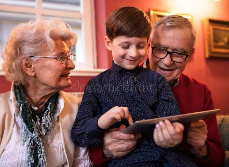 Pares mayores que se relajan con su nieto mientras que usa la tableta imagen de archivo