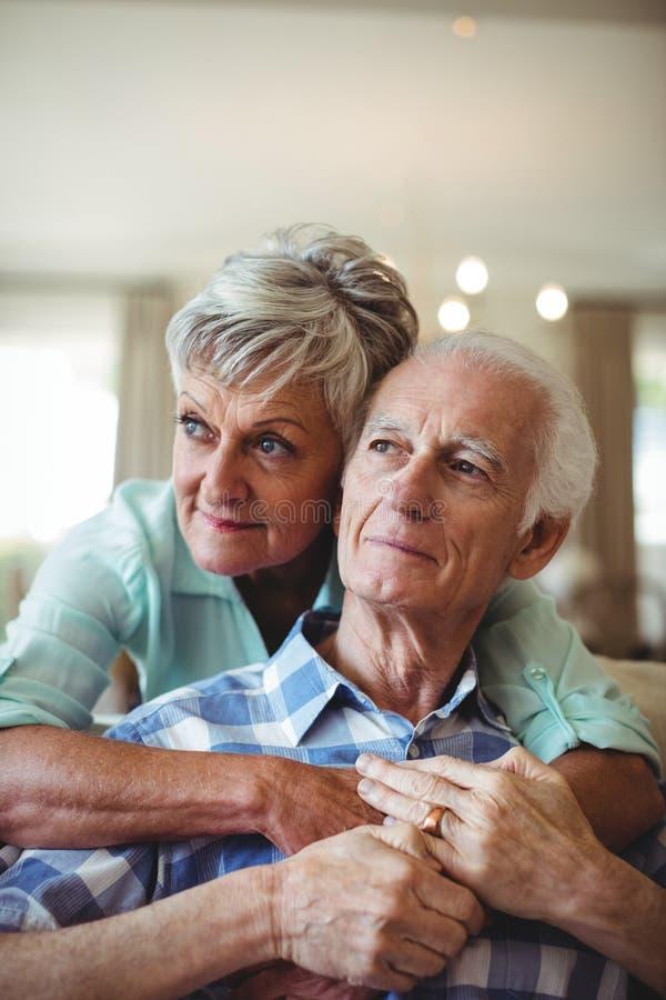 Pares mayores que se relajan en el sofá en sala de estar fotos de archivo libres de regalías
