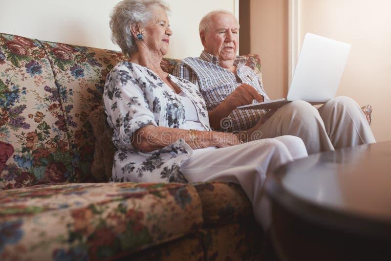 Pares mayores que se relajan en el sofá y que usan el ordenador portátil fotos de archivo