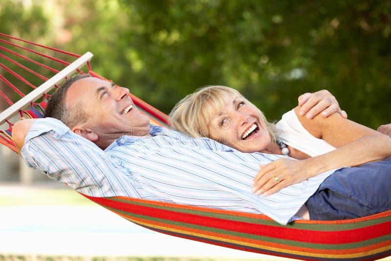Pares mayores que se relajan en hamaca imagen de archivo libre de regalías