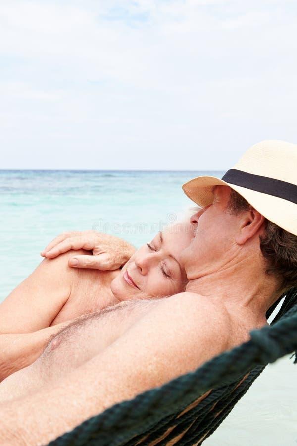 Pares mayores que se relajan en hamaca de la playa fotografía de archivo