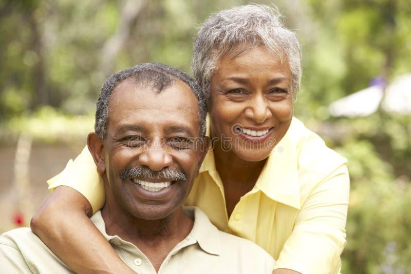 Pares mayores que se relajan en jardín fotos de archivo libres de regalías