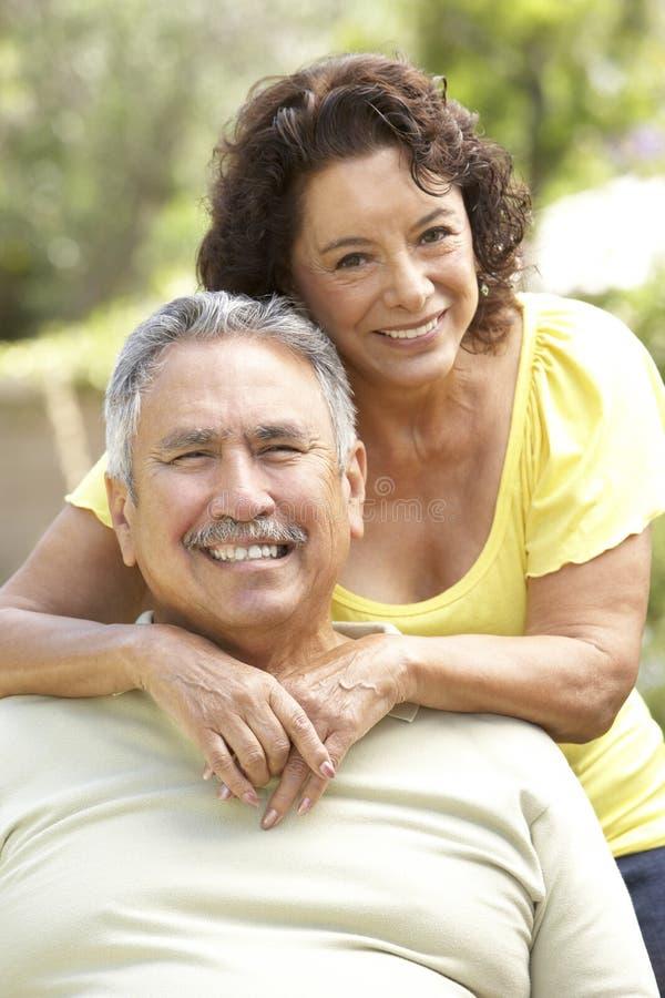 Pares mayores que se relajan en jardín junto foto de archivo